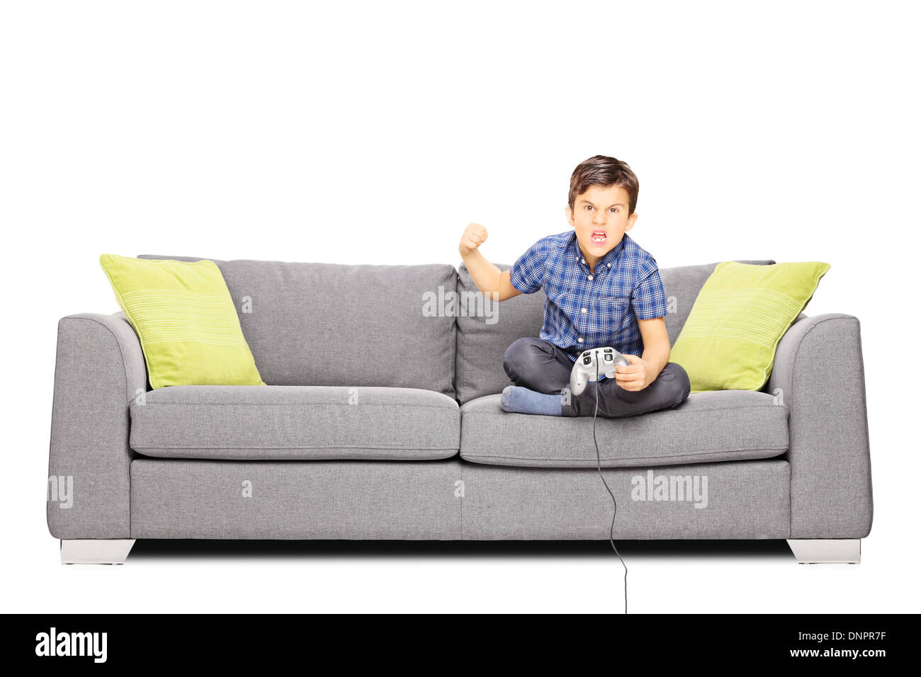 Nervous kid sitting on sofa and playing video games Stock