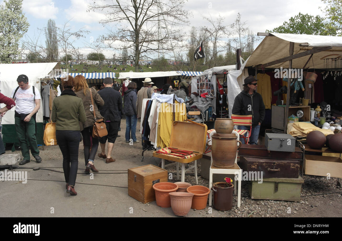 Sunny view people walking concrete pathway by canopy stall with plant pots l&s vendor Mauerpark Flea Market Berlin & Sunny view people walking concrete pathway by canopy stall with ...