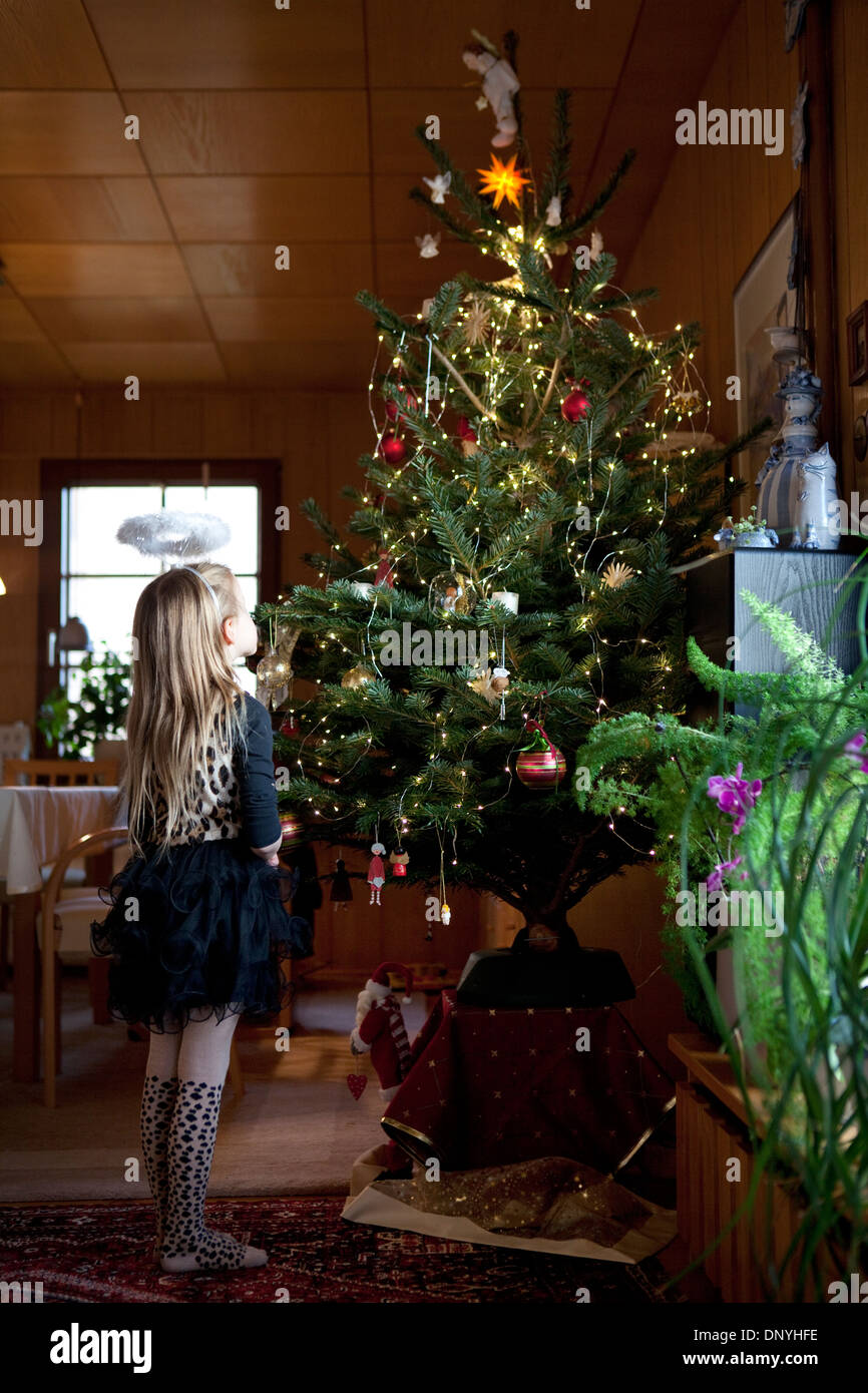 Young girl looking up at the star and angel on top of a for Best looking christmas tree