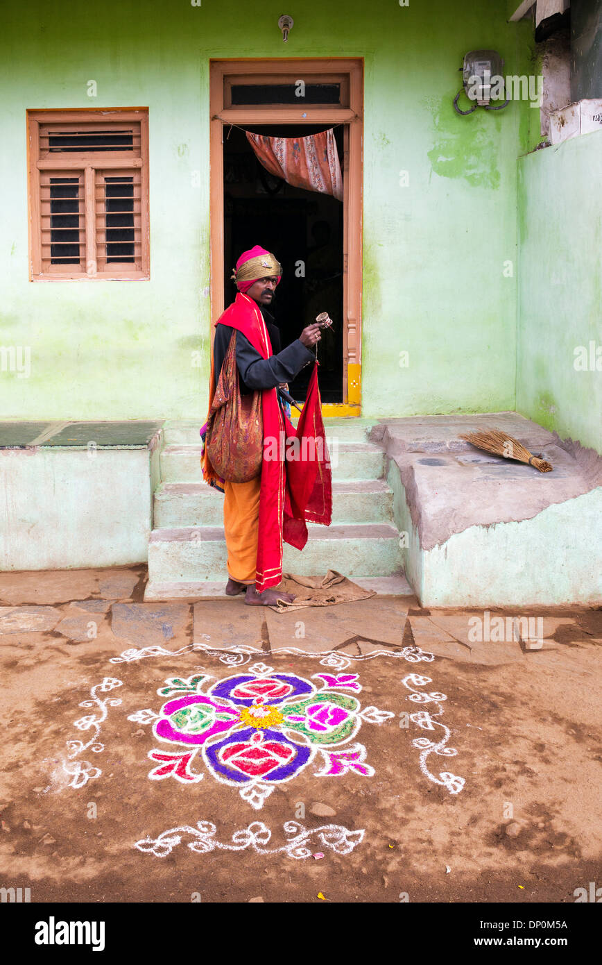 Indian Religious Beggar Begging Outside A Rural Village House In Front Of A  Rangoli Festival Design. Andhra Pradesh, India