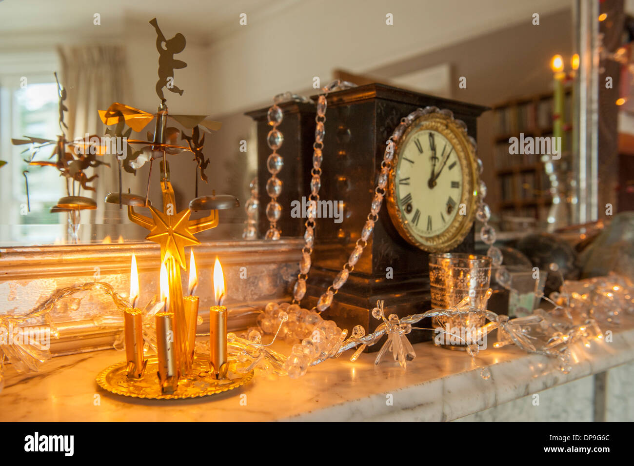 an antique clock above a fireplace with a christmas candle chime