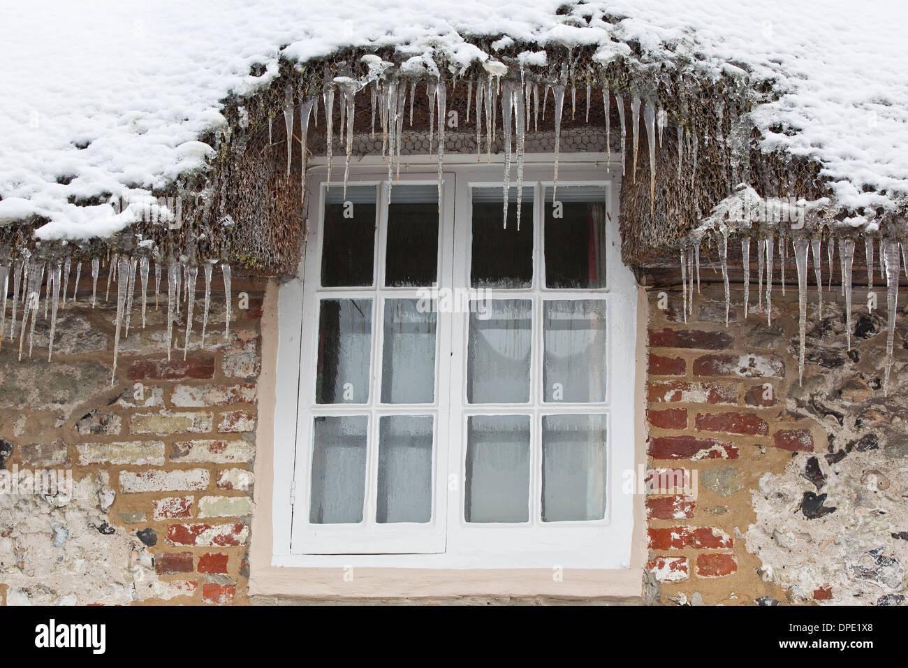 A Row Of Icicles Hanging From Thatched Roof Around Window On Cottage