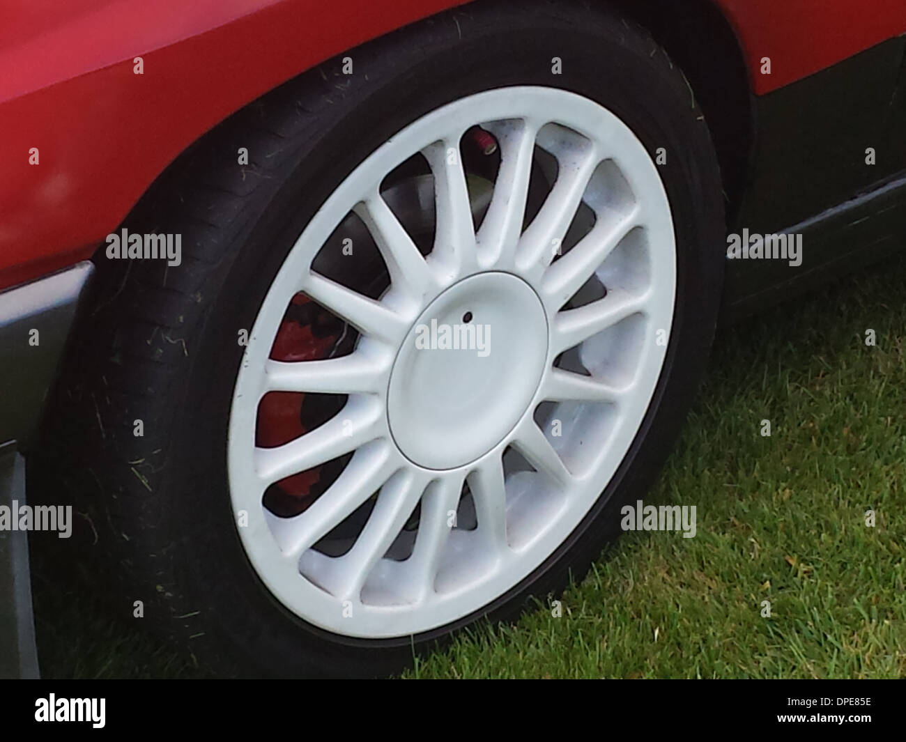 close up of a white alloy wheel with red brake calipers behind fitted to a 1980s hot hatch vauxhall opel nova gte corsa