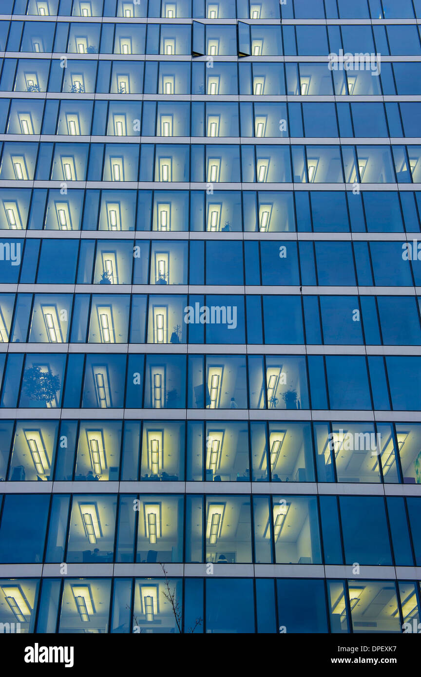 Facade of a modern office building with lights on in the offices