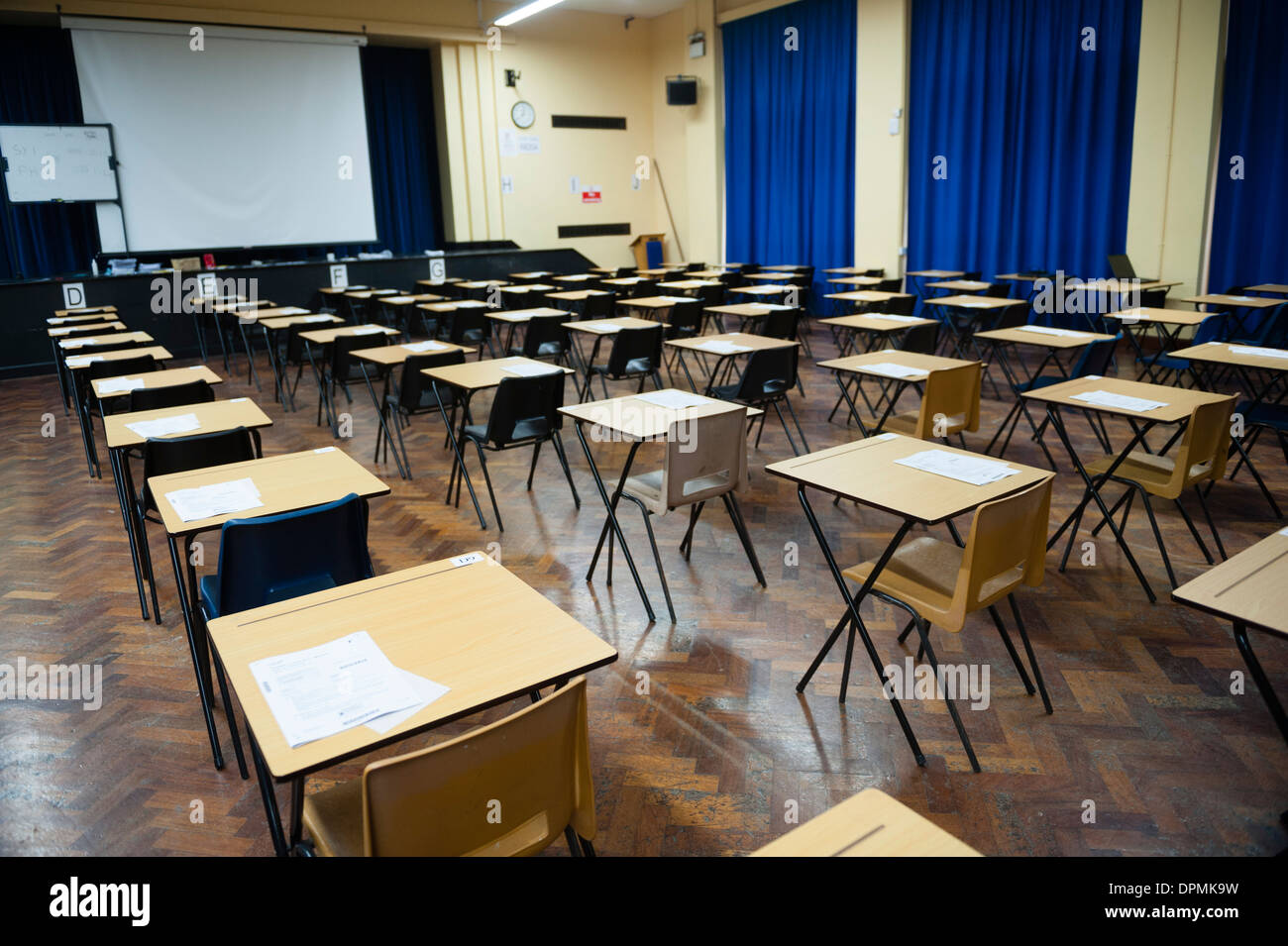 rows of desks with examinations ready in school gymnasium stock