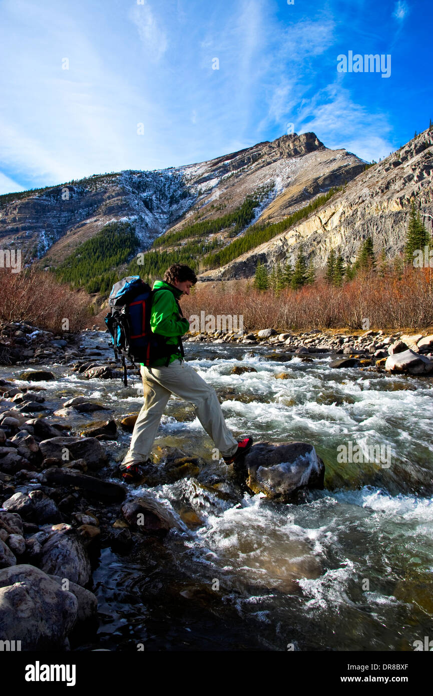 A male hiker crossing a fast flowing stream in the ...