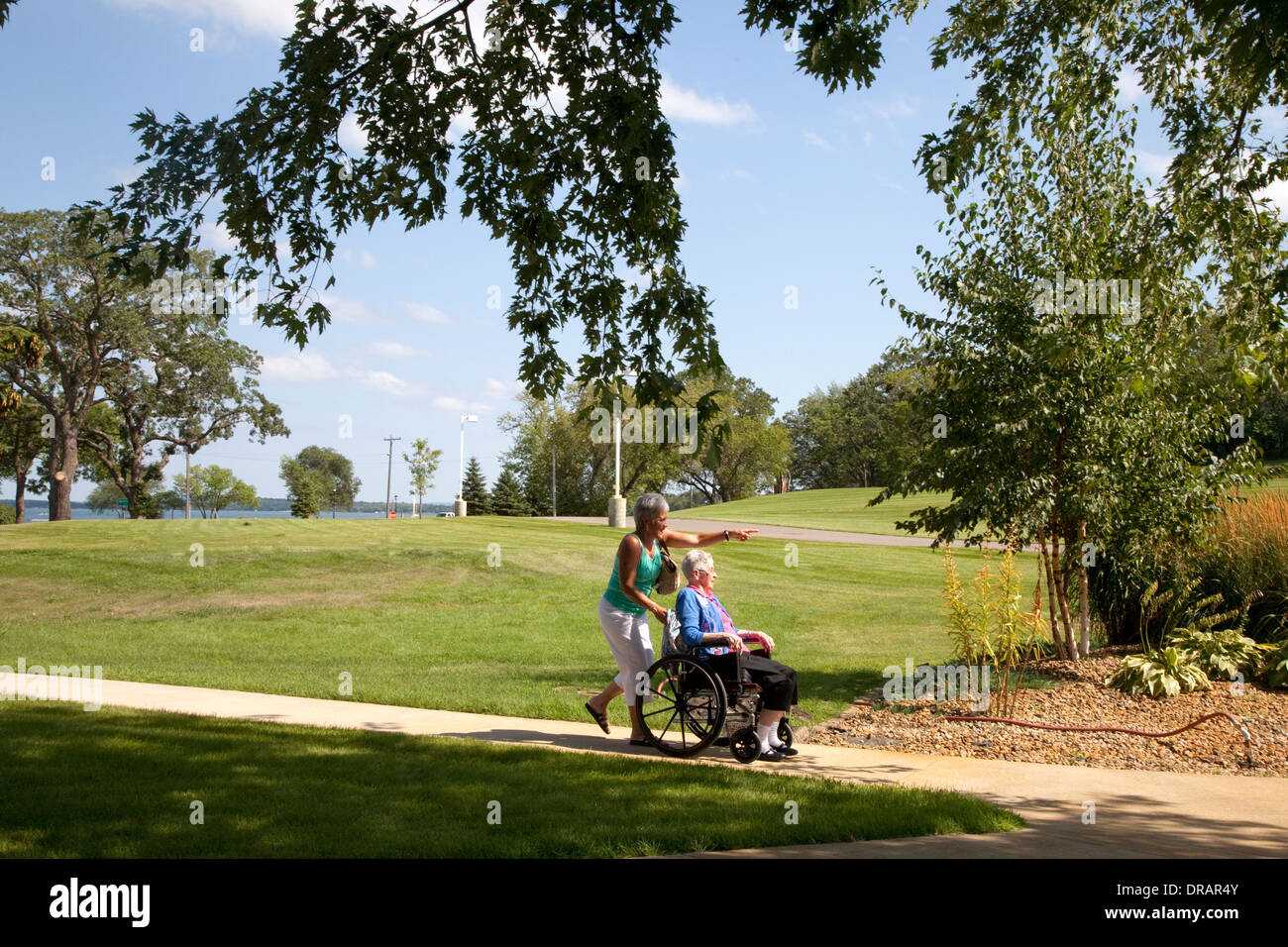 Elderly Woman Pushed In Wheelchair Through Nursing Home Park Battle Lake Minnesota MN USA