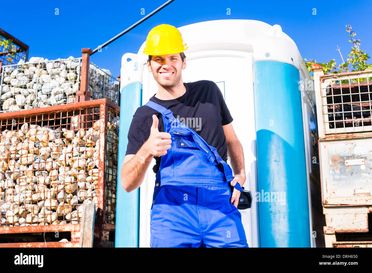 Stock Photo   builder using mobile restroom or chemical toilet on  construction or building site. builder using mobile restroom or chemical toilet on construction