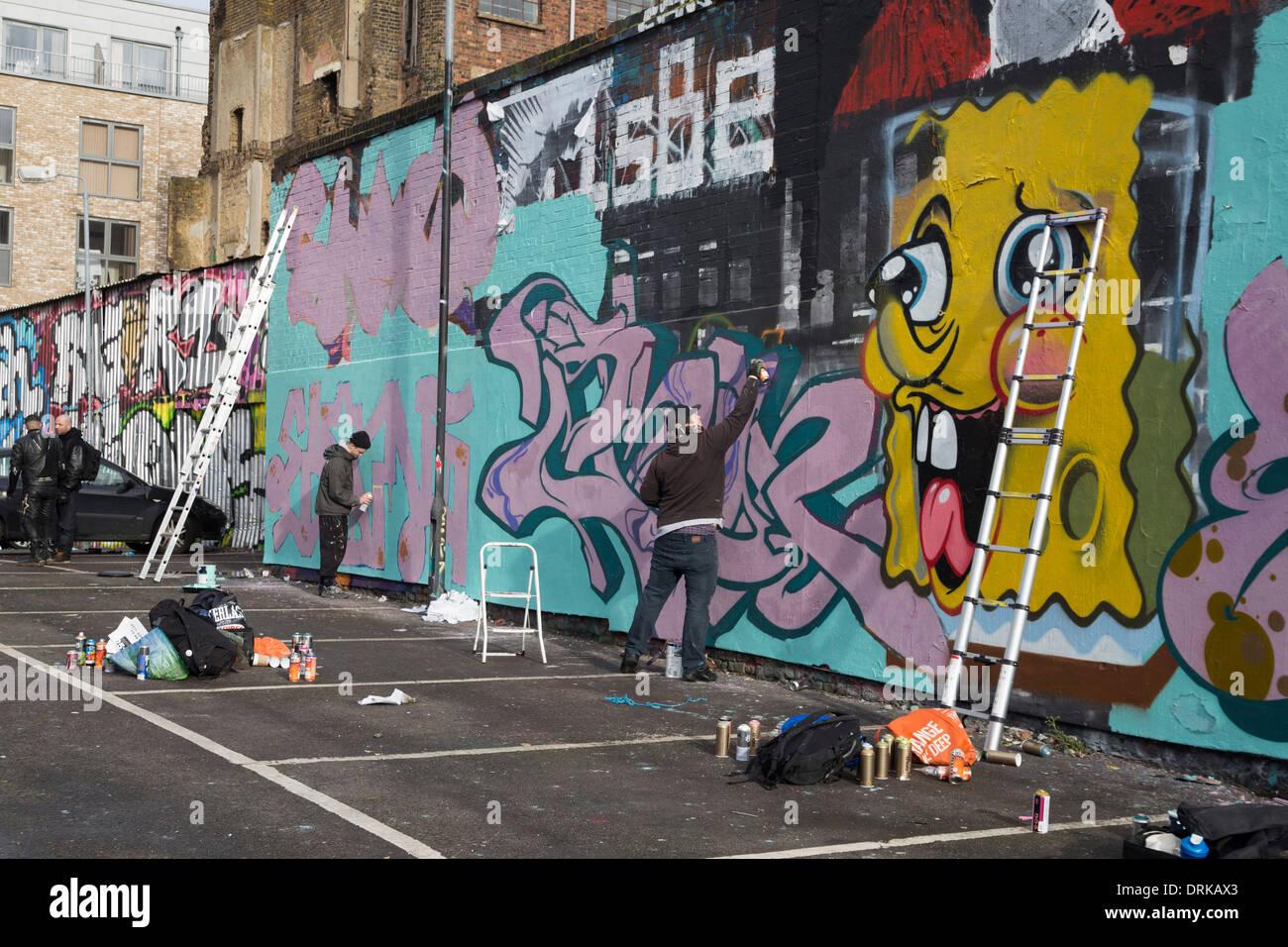 Grafitti wall painting - Graffiti Wall In Shoreditch London Graffiti Artists Working Spray Painting Wall
