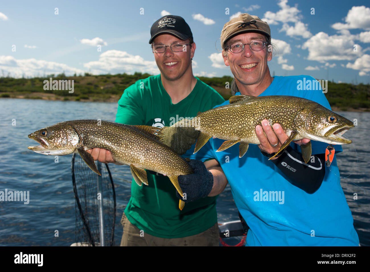 Fishing buddies hold up their summer lake trout catch in a for How to catch fish in a lake