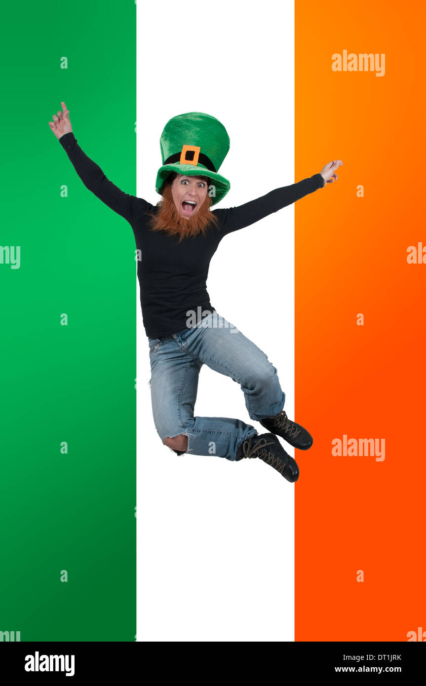 a happy leprechaun jumping in front of an irish flag stock photo
