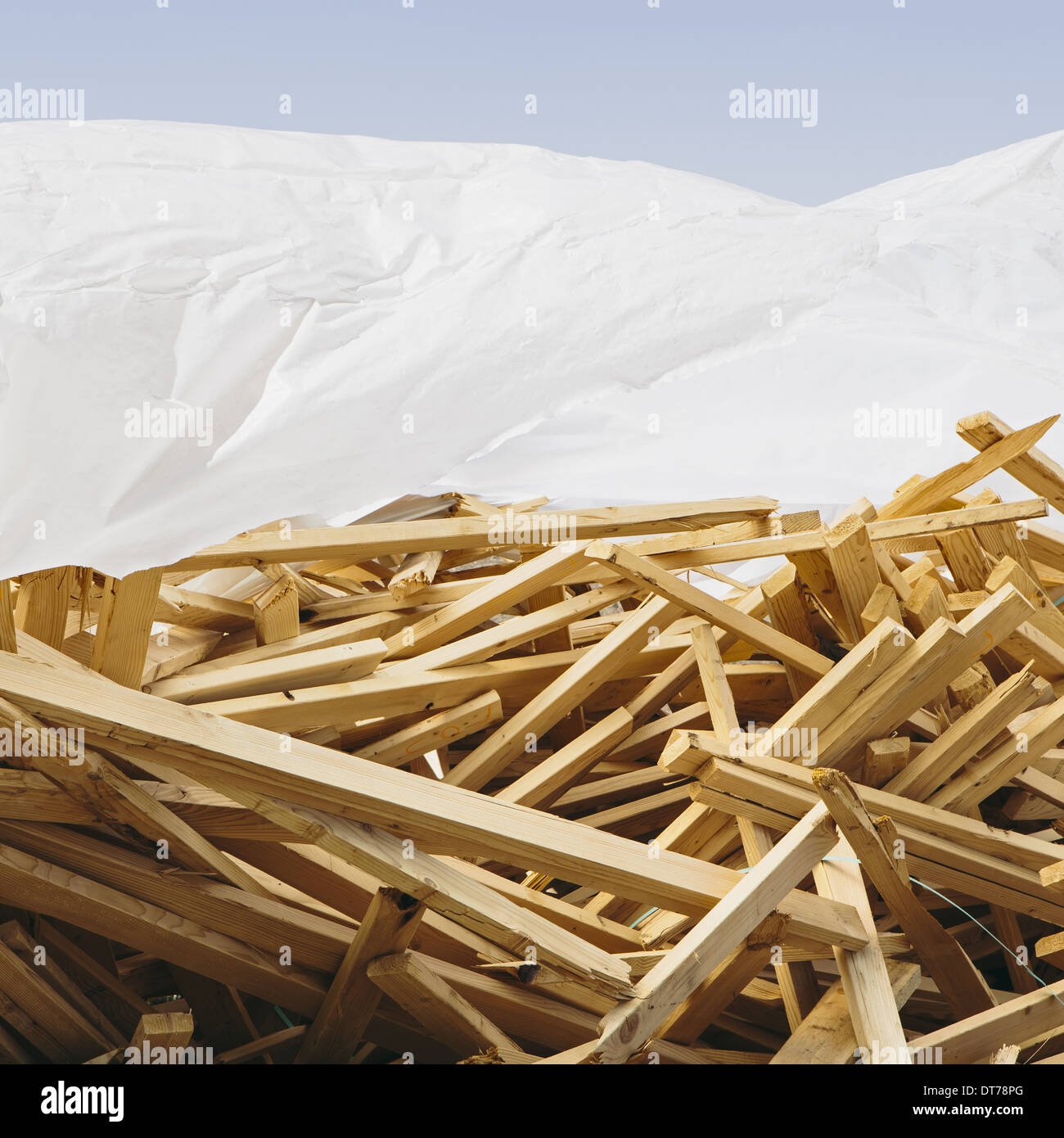 Wood Piling Construction : White tarp covering pile of wood studs used for