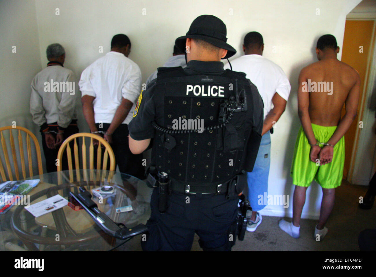 Detroit police narcotics officer searches men during a raid Stock ...