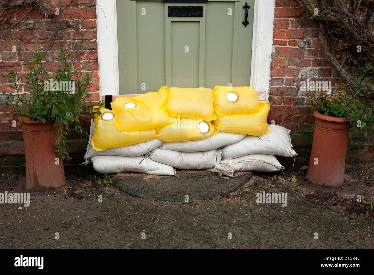 A sage green front door with sand bags, flood protection Stock ...