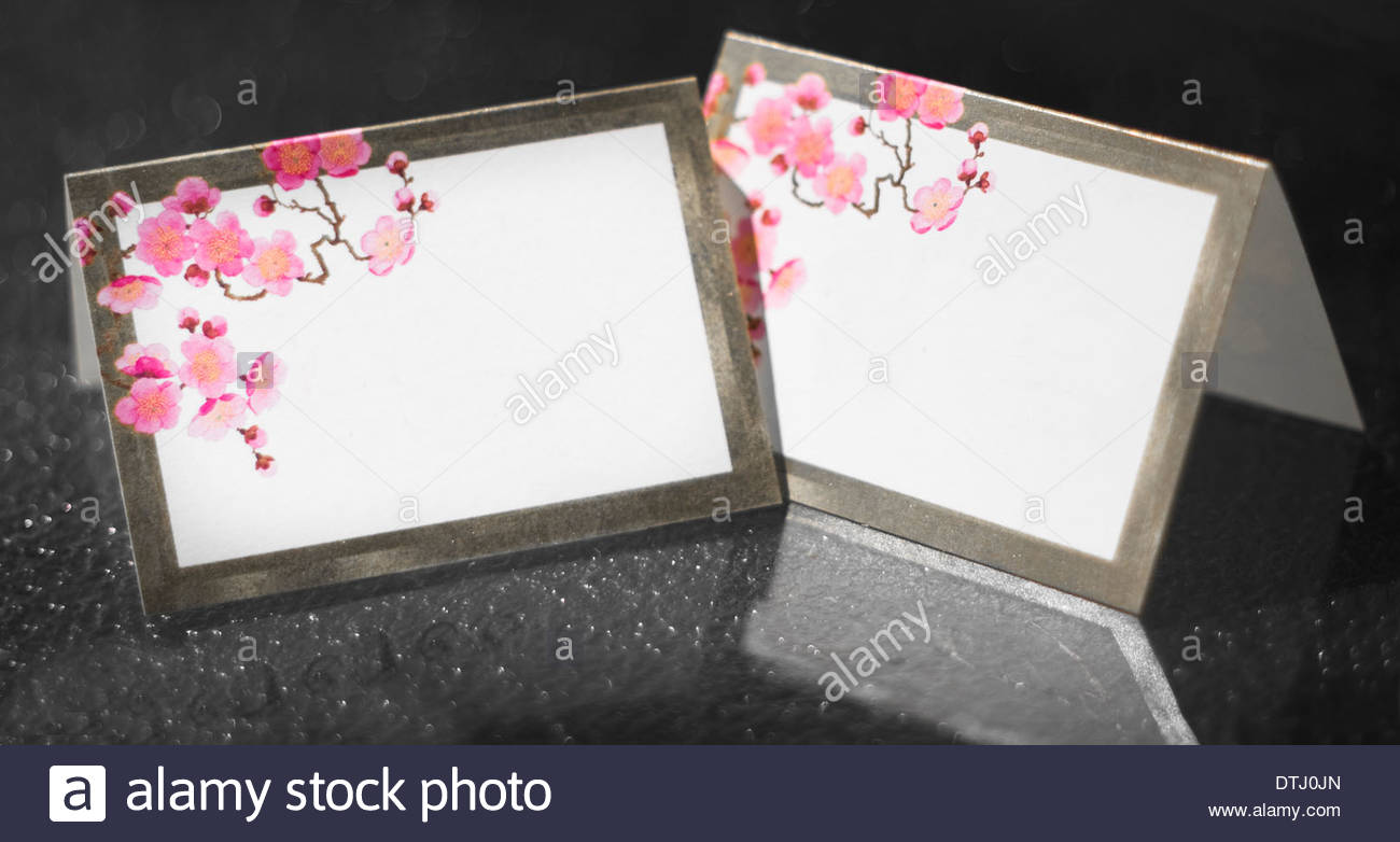 blank wedding reception table place cards for seating arrangement sitting on a glass table