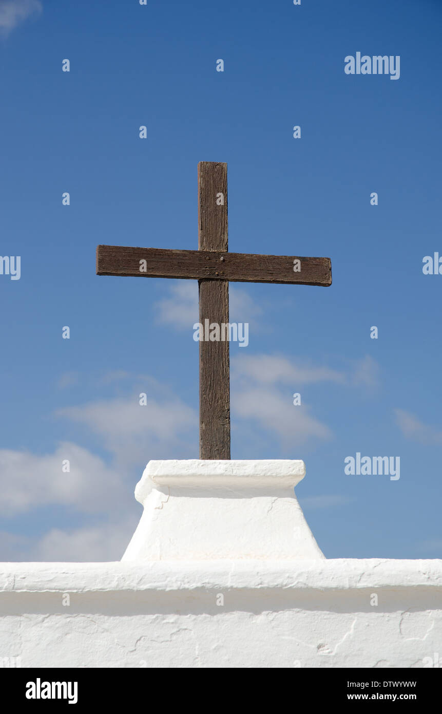 Wooden cross symbol of religion in spain which is a catholic wooden cross symbol of religion in spain which is a catholic country against a white wall and blue sky buycottarizona