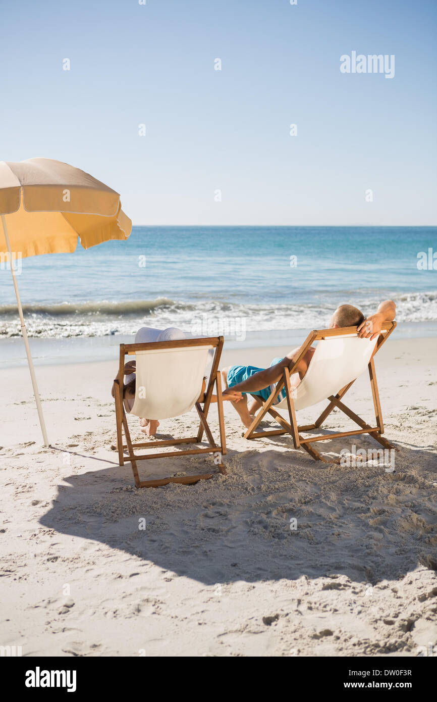 Awesome Happy Couple Sunbathing On Their Deck Chairs
