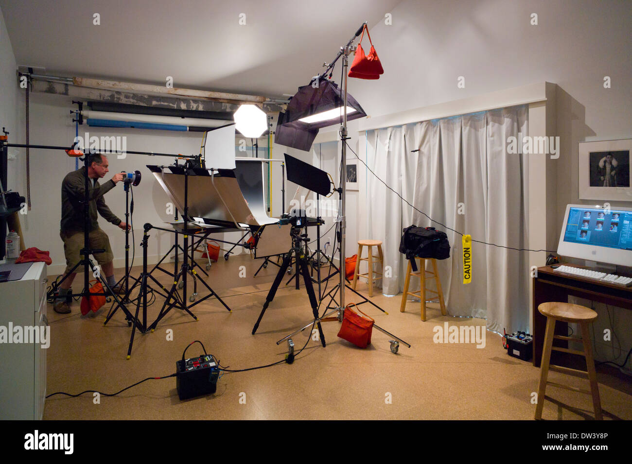 Photographer working in a commercial photography studio with stock photographer working in a commercial photography studio with lighting background and grip gear aloadofball Images