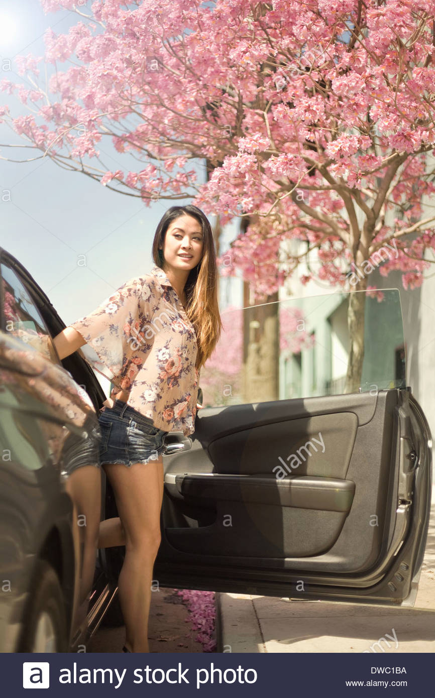 Stock Photo - Young woman stepping out of car door