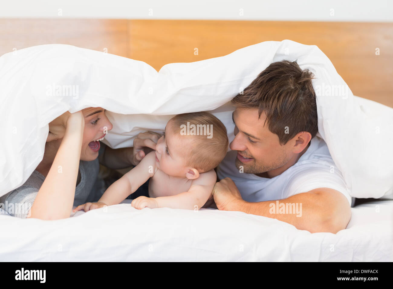 Baby bed with parents - Happy Parents Lying On Bed With Baby Son