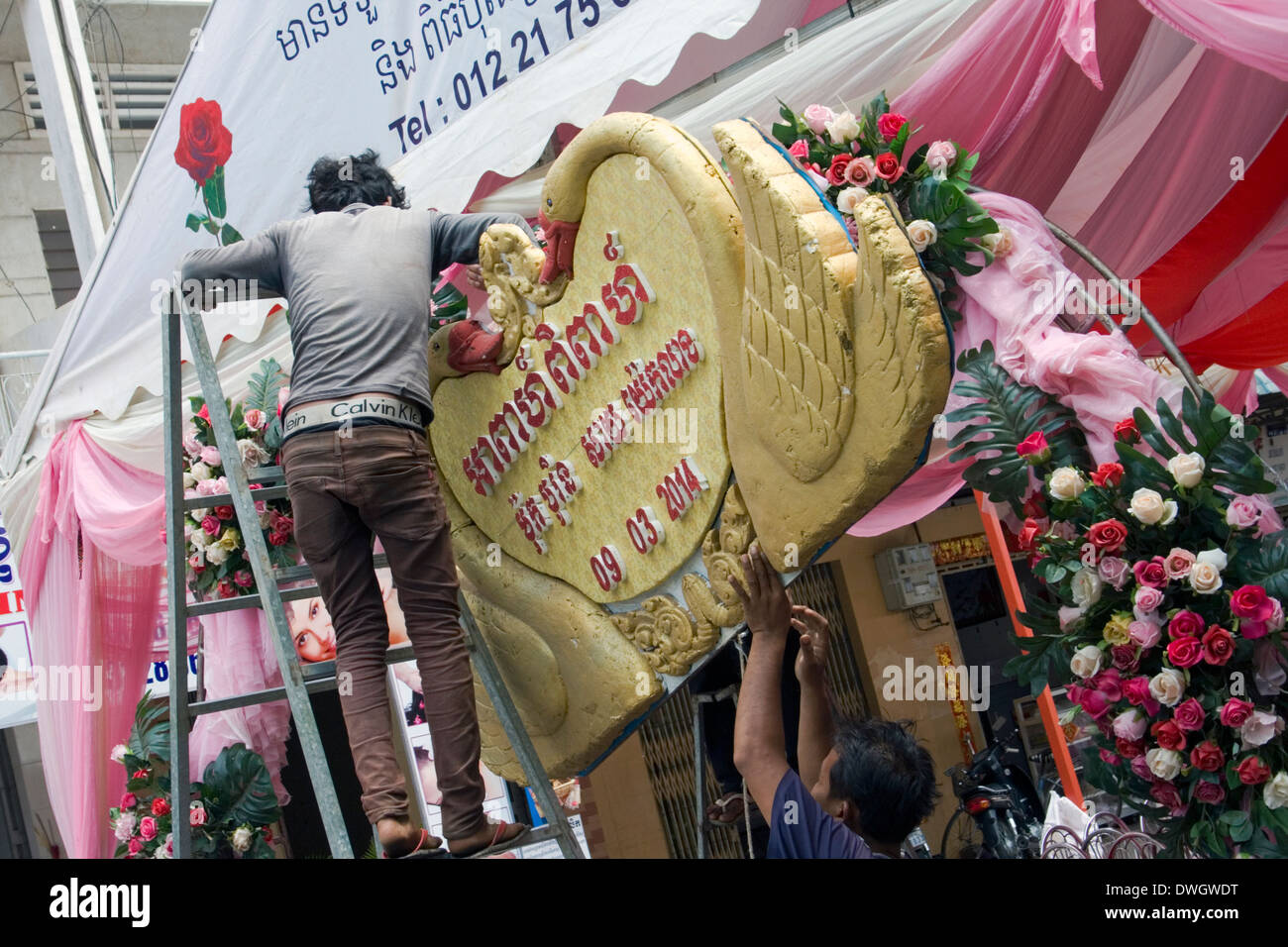 Men are hanging a sign on a wedding tent before a marriage ceremony on a city street in K&ong Cham Cambodia & Men are hanging a sign on a wedding tent before a marriage ...