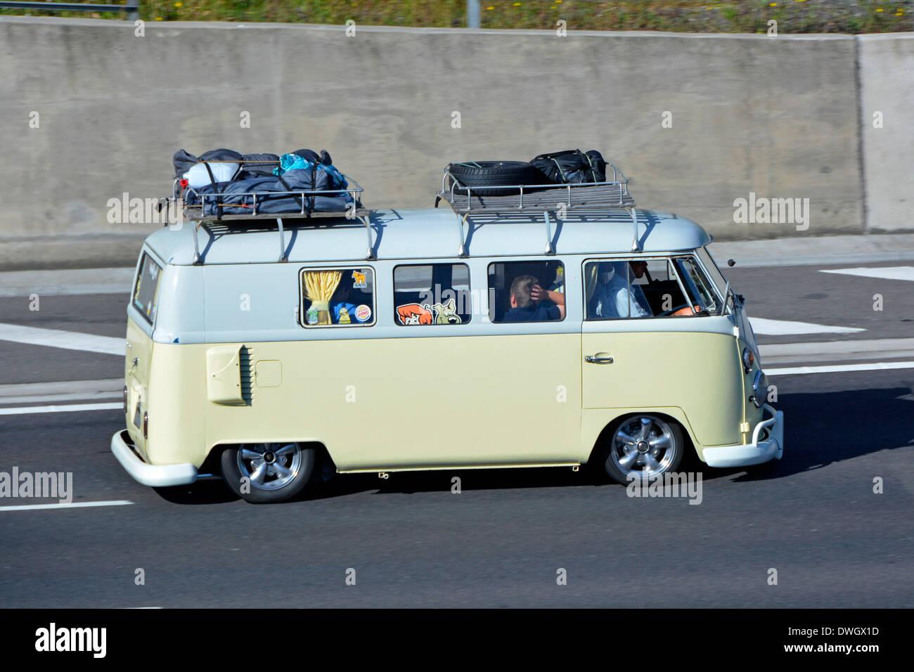 Loaded Roof Racks On Low Slung VW Camper Van Driving Along Motorway