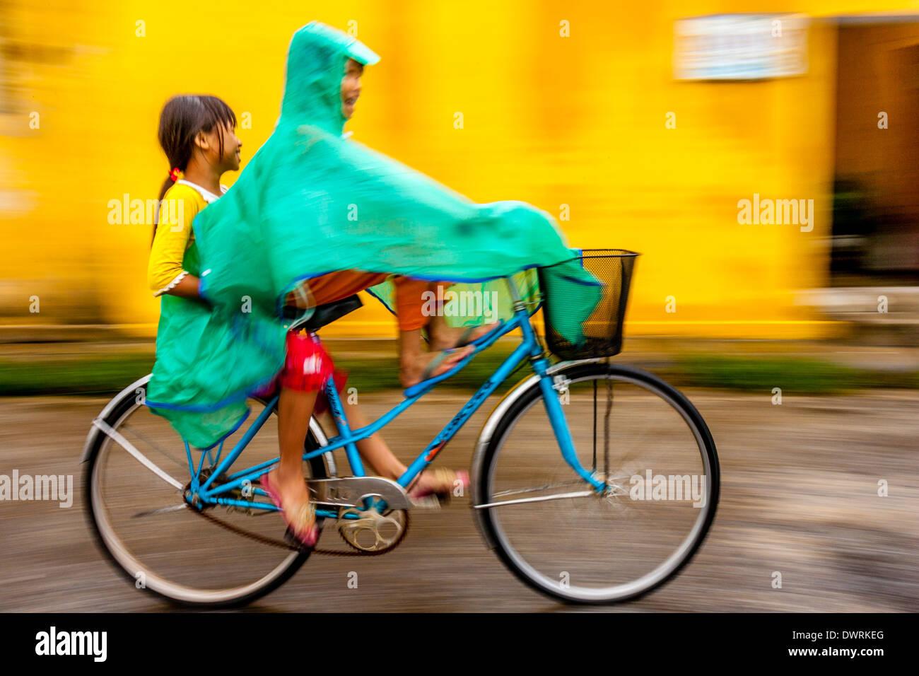Two Girls Riding A Bike In The Rain Hoi An Vietnam Stock Photo