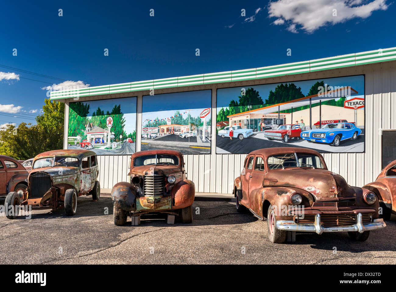 Old, rusted cars for sale, murals behind on wall of service ...