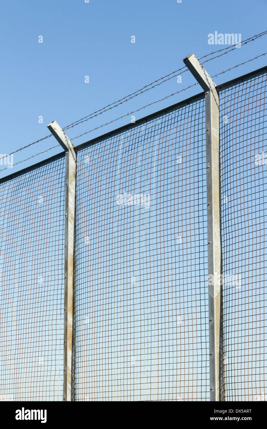Tall Wire Mesh Security Fence On Concrete Posts Topped
