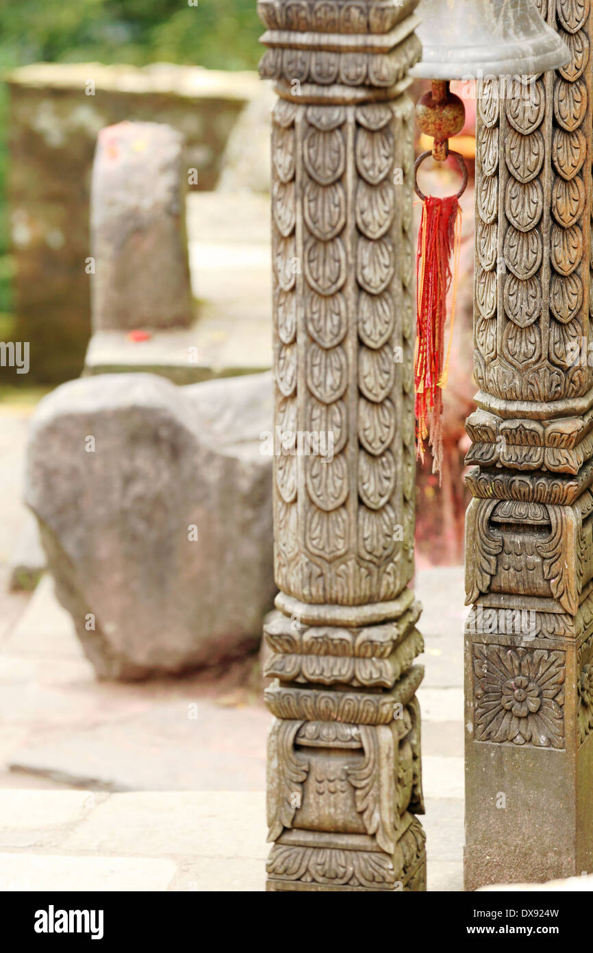 Small Wooden Column : Carved wooden columns holding small bronze bell