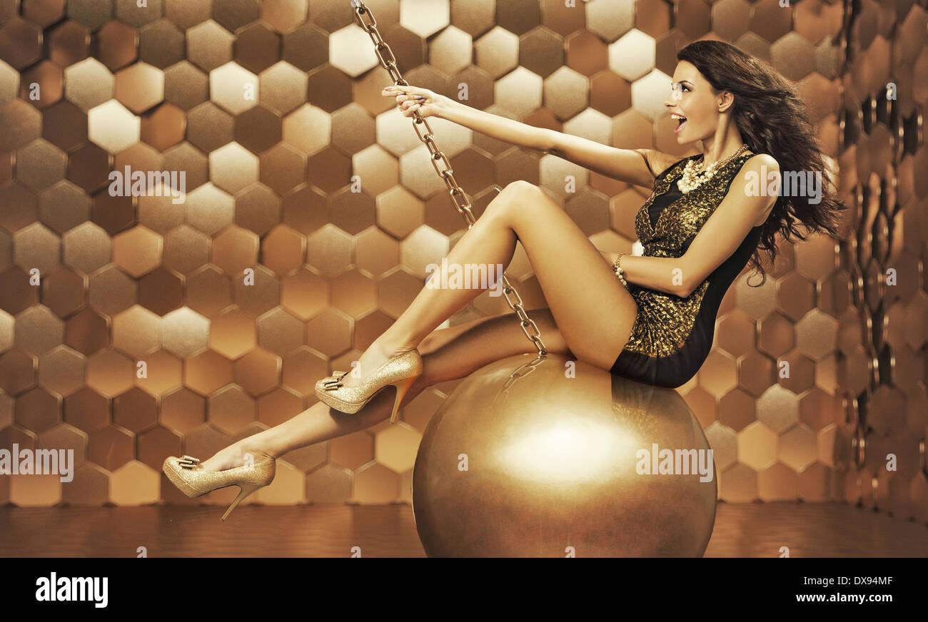 sexy-woman-on-a-big-gold-ball-DX94MF.jpg