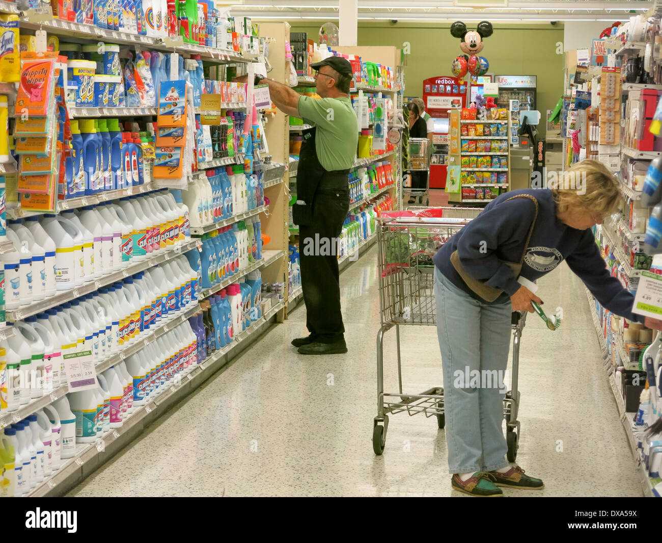 Employee Stocking Shelves and Woman Shopping, Cleaning Products ...