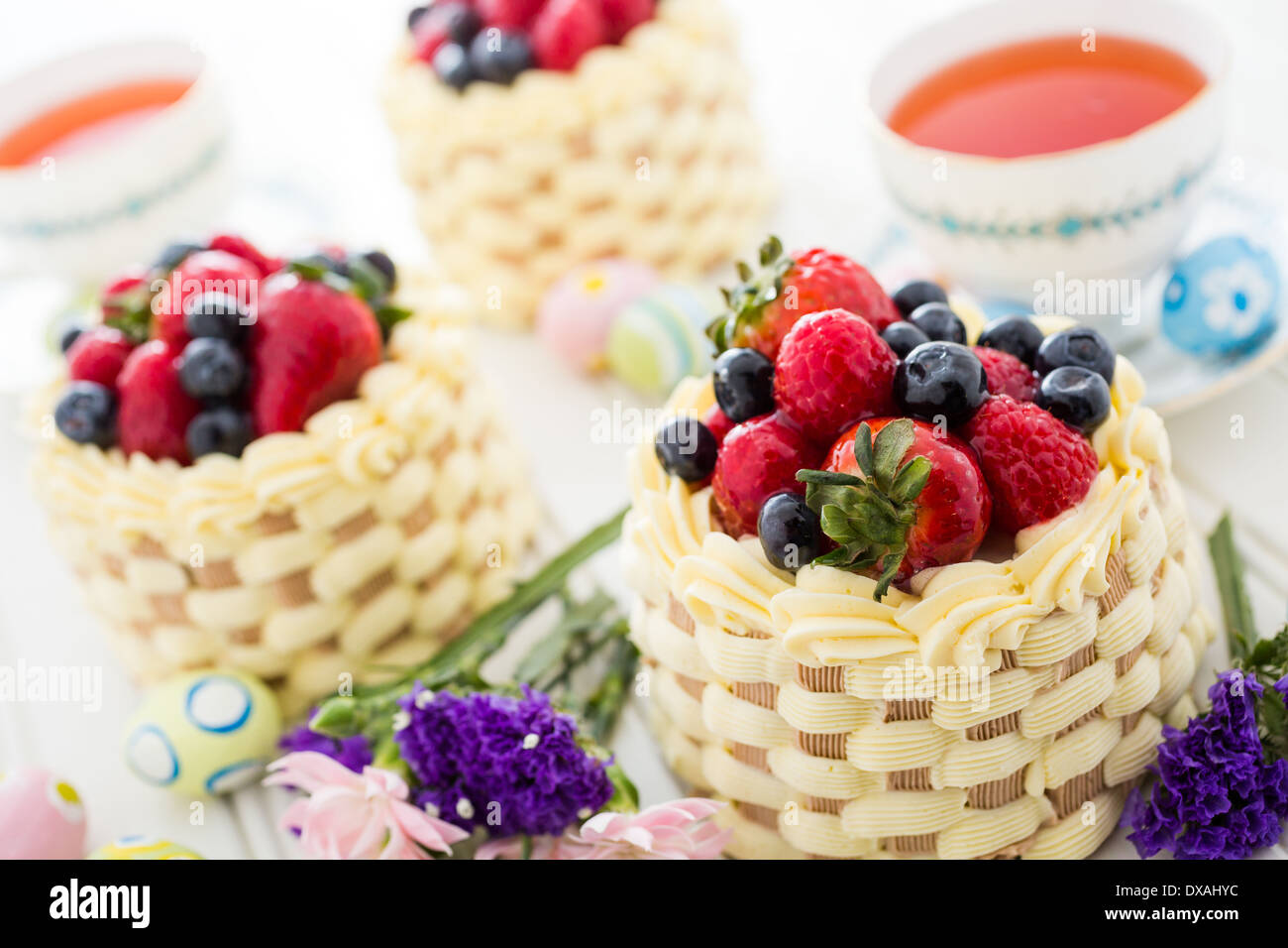 Easter basket mini cakes with glazed fresh fruit on top Stock