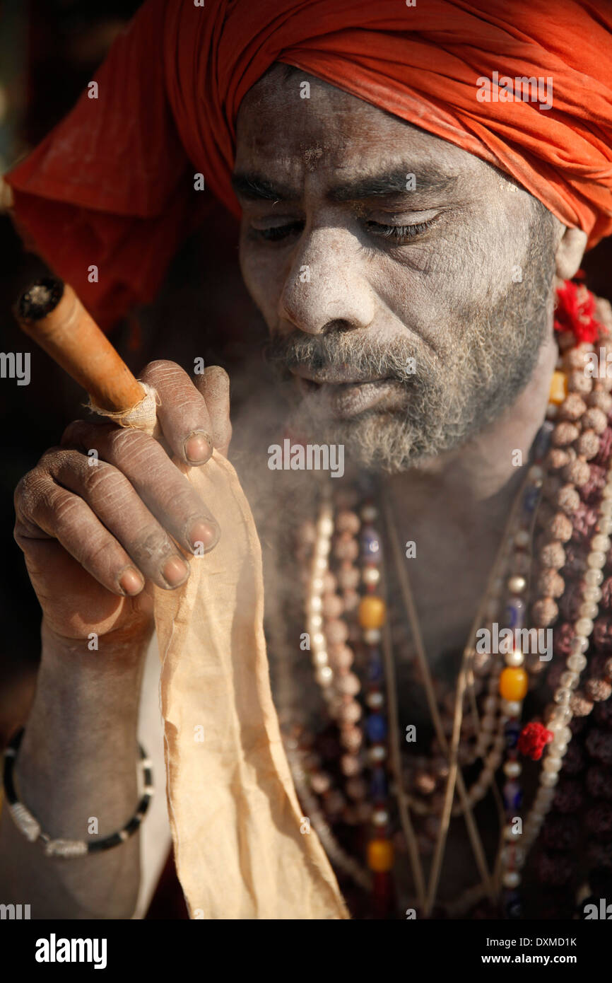 India, Uttar Pradesh, Varanasi, portrait of Sadhu smoking ...
