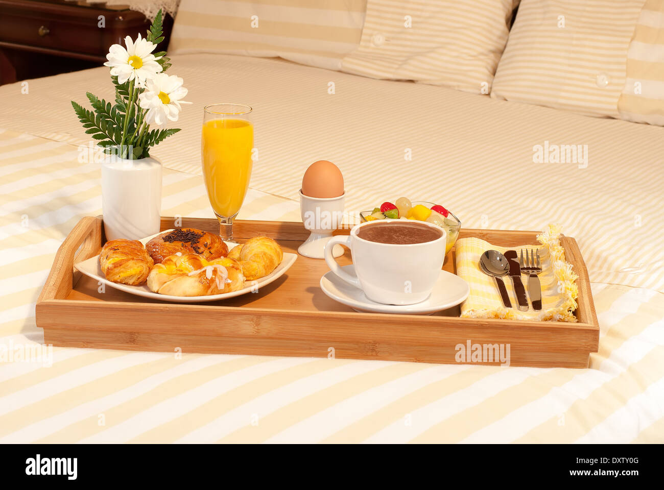 full breakfast tray with flowers on the bed stock photo, royalty