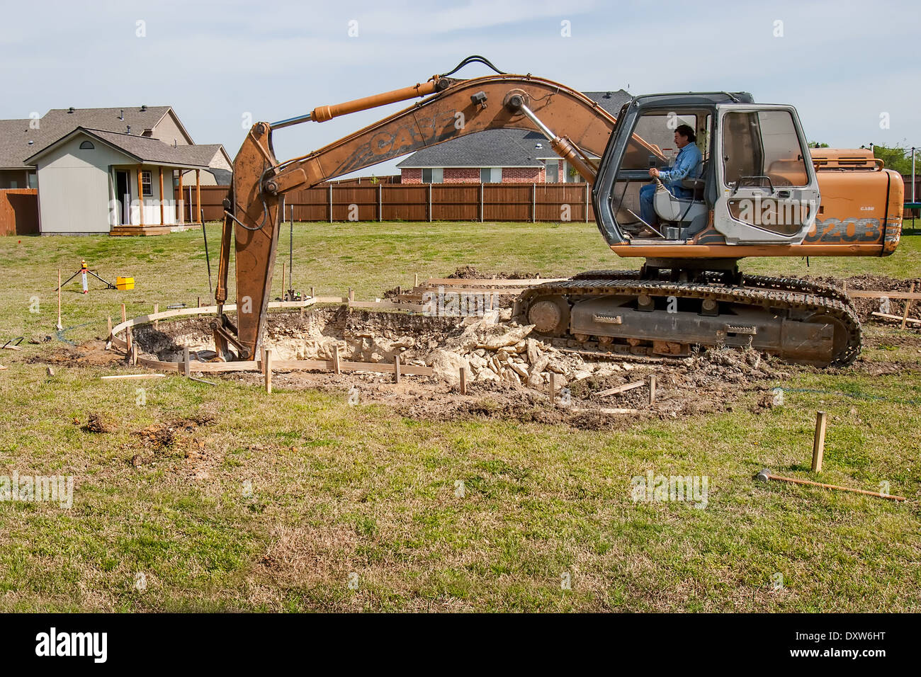 digging a pool in the backyard with a backhoe stock photo royalty