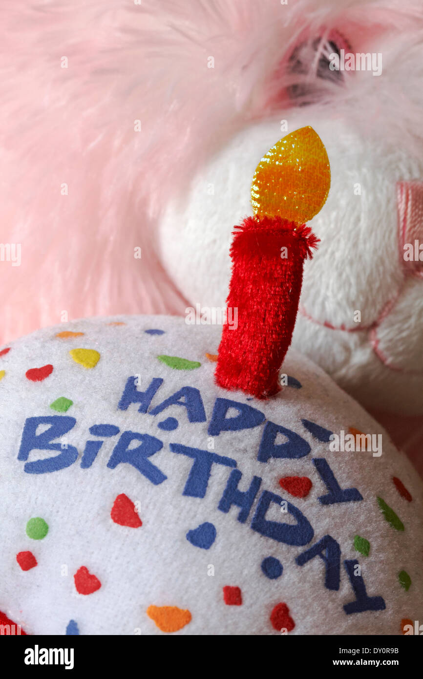 pink teddy bear holding happy birthday cake with lit candle stock