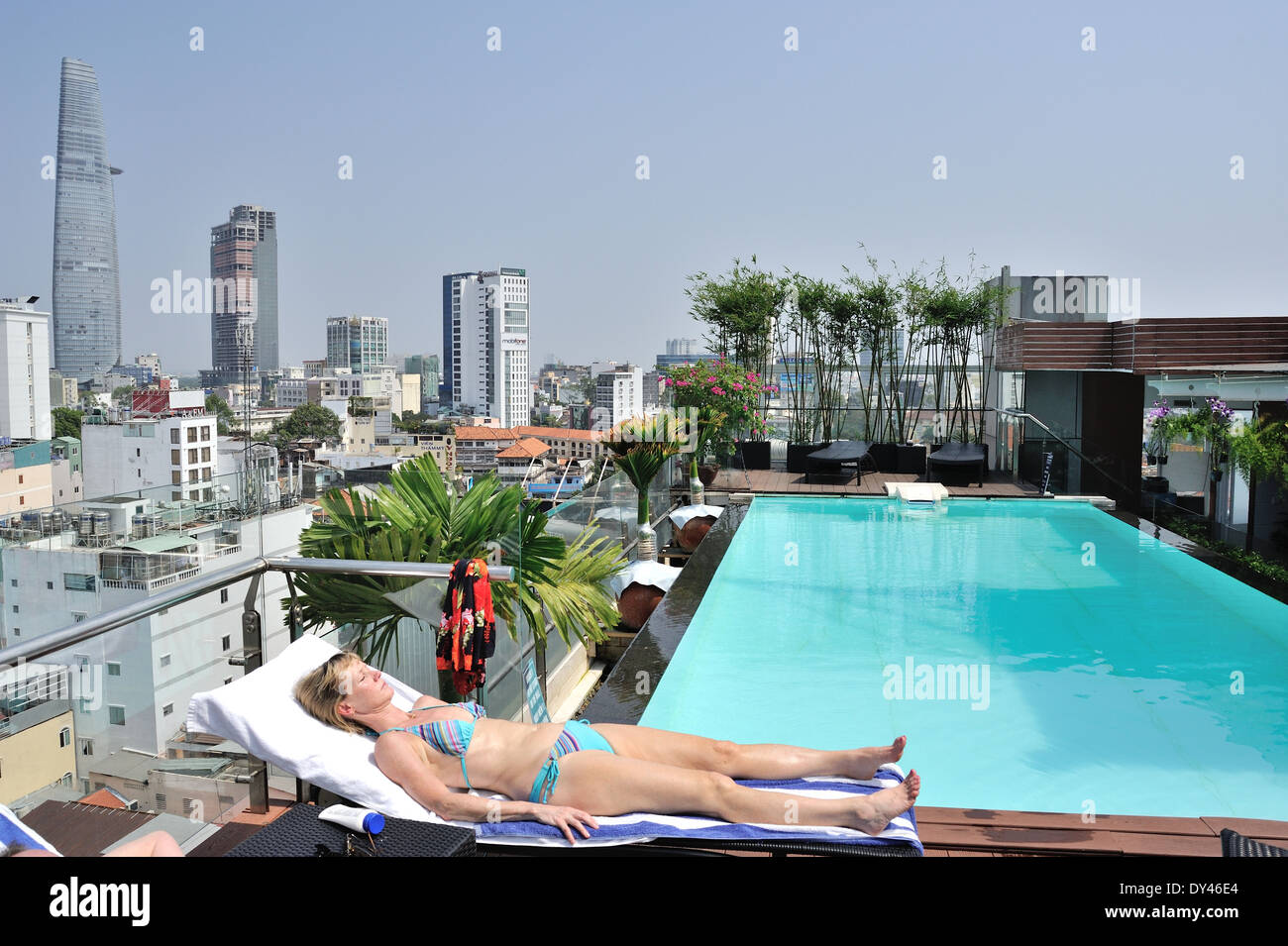 Tourist sunbathing on rooftop pool ho chi minh city saigon Ho chi minh city hotels with swimming pool