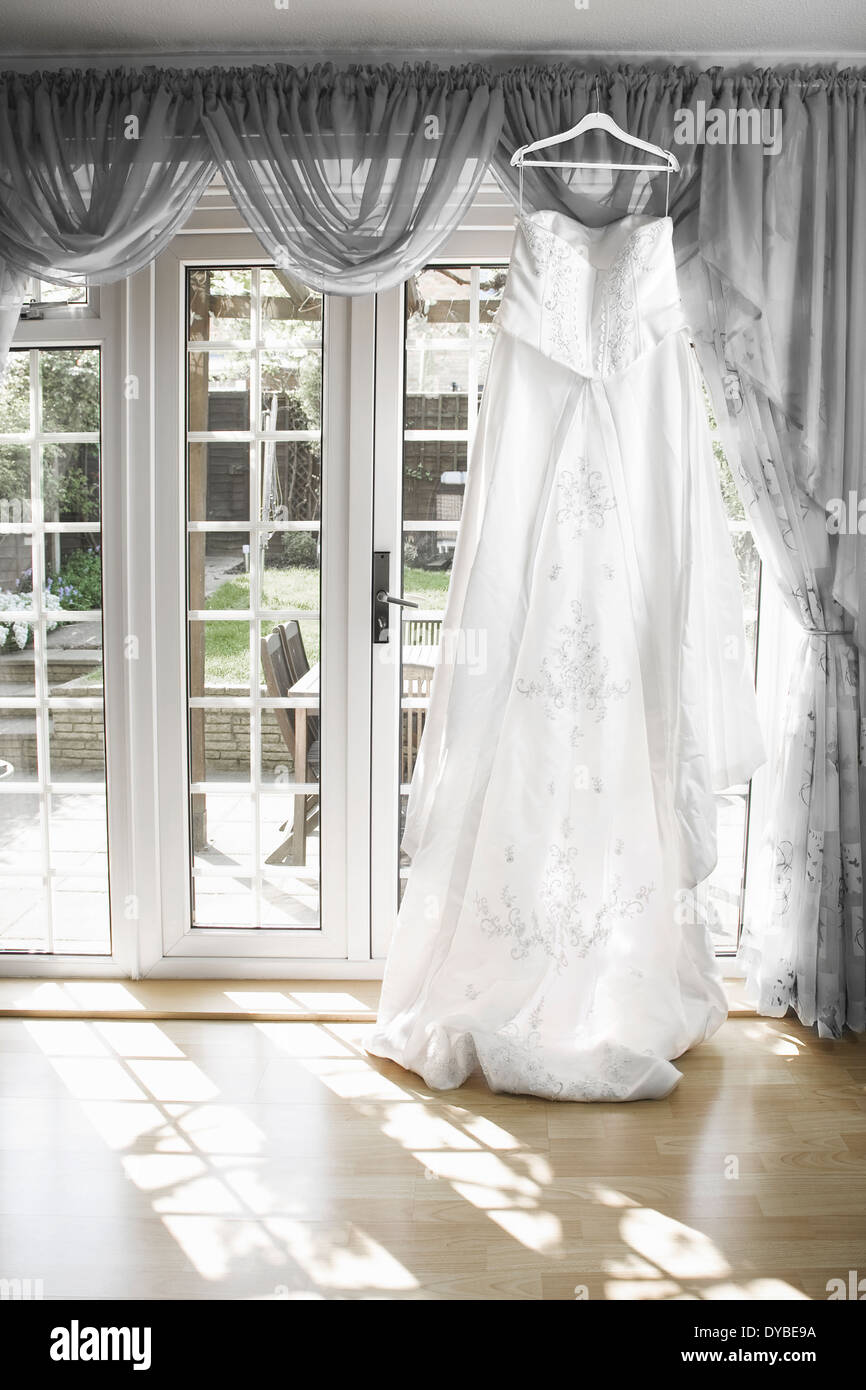 See sun shining through dress - Stock Photo White Wedding Dress Hanging From A Curtain Pole With The Sun Shining Through The Window