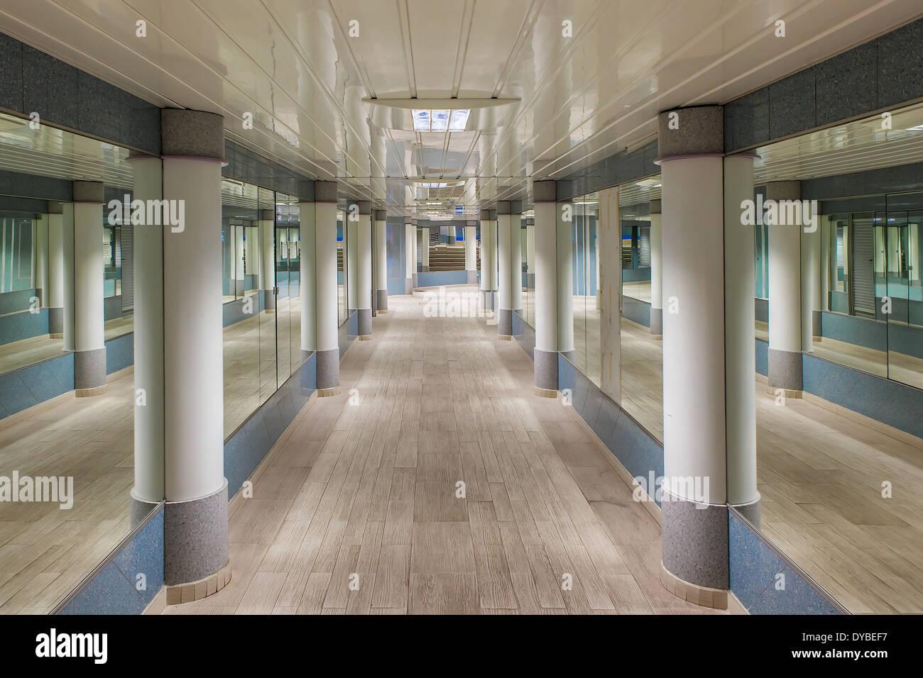 View of modern underground pedestrian passage with mirrors on ...