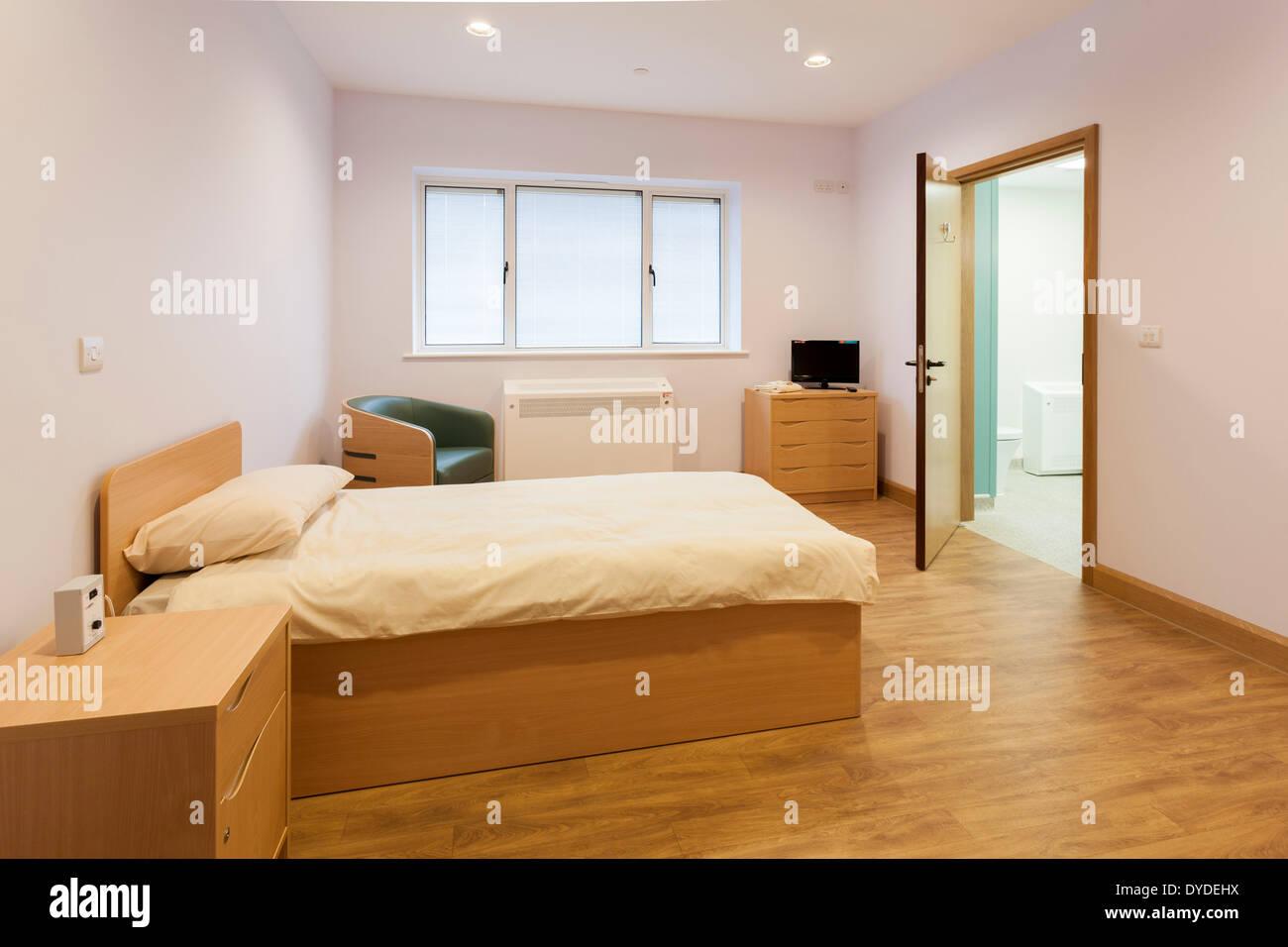 Unoccupied care home bedroom with open door to en suite bathroom. Unoccupied care home bedroom with open door to en suite bathroom