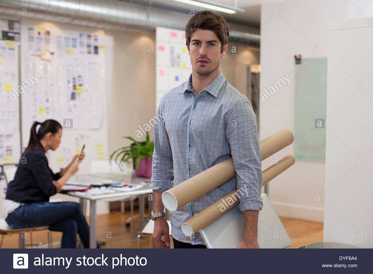 Portrait architect holding blueprint tubes in office stock photo portrait architect holding blueprint tubes in office malvernweather Images