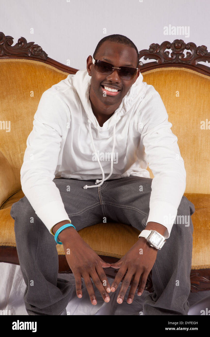 Handsome Black Man In Sunglasses, Sitting On A Gold Couch And Smiling At  The Camera