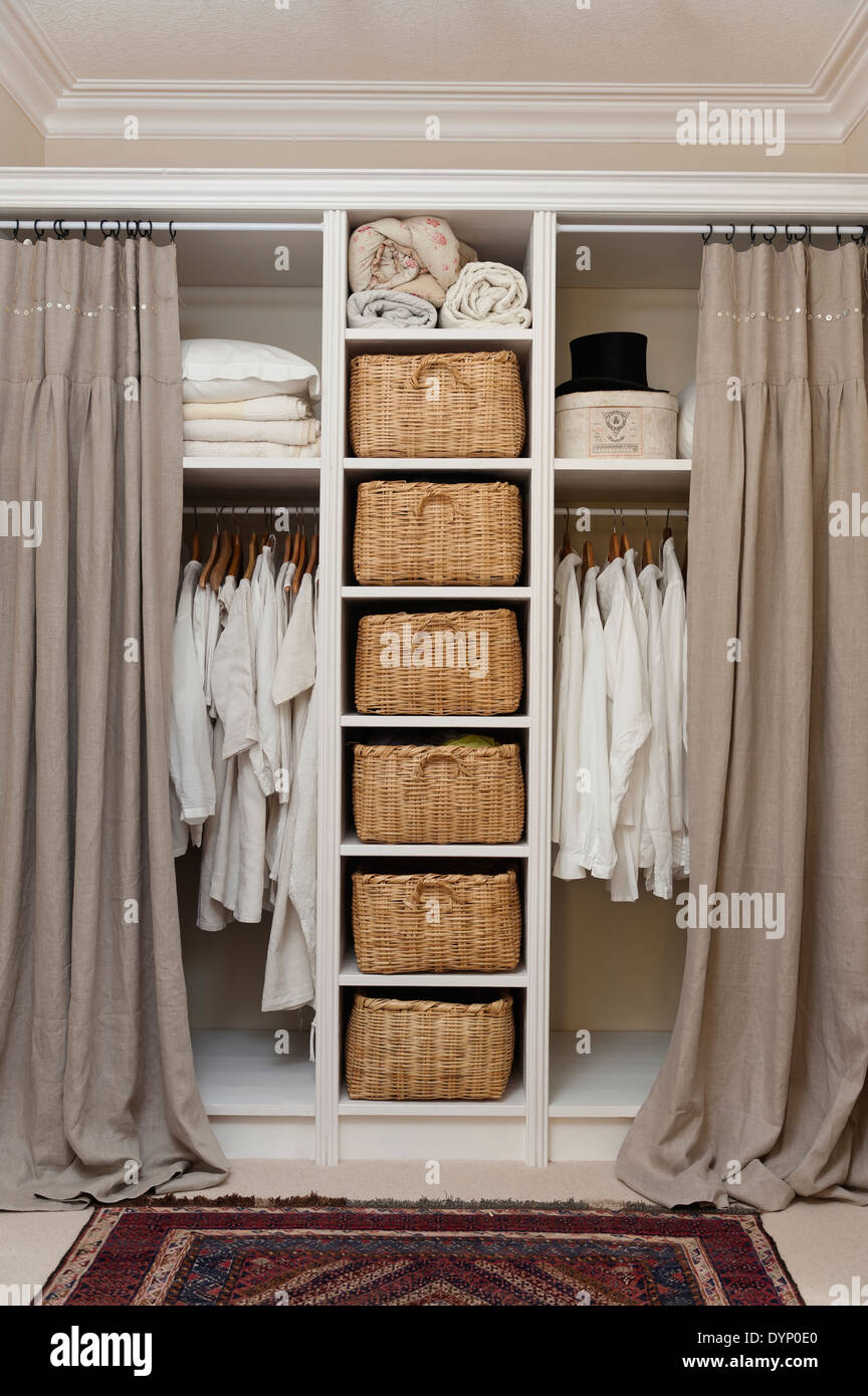 Wicker storage baskets on shelving in cream painted fitted unit in ...