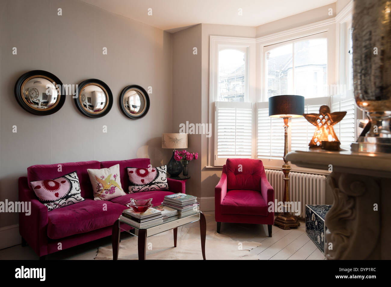 ... Raspberry Coloured Velvet Furniture In Living Room With Graham And  Green Porthole Wall Mirrors   Stock
