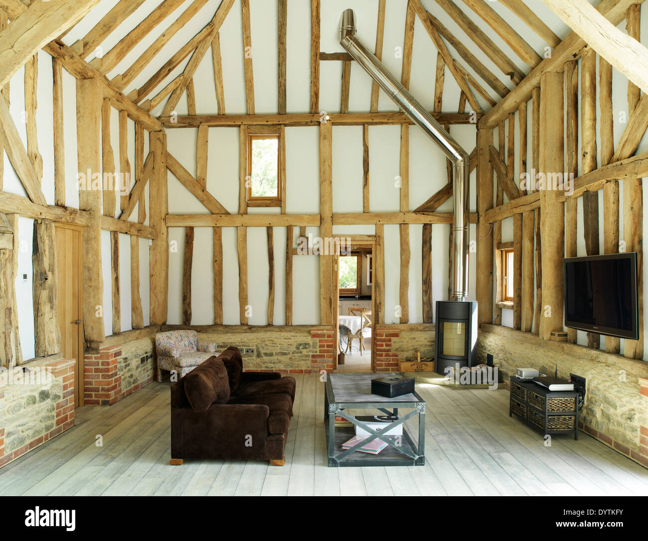 Living room in barn conversion with exposed beams, Field Place Barns, Surrey