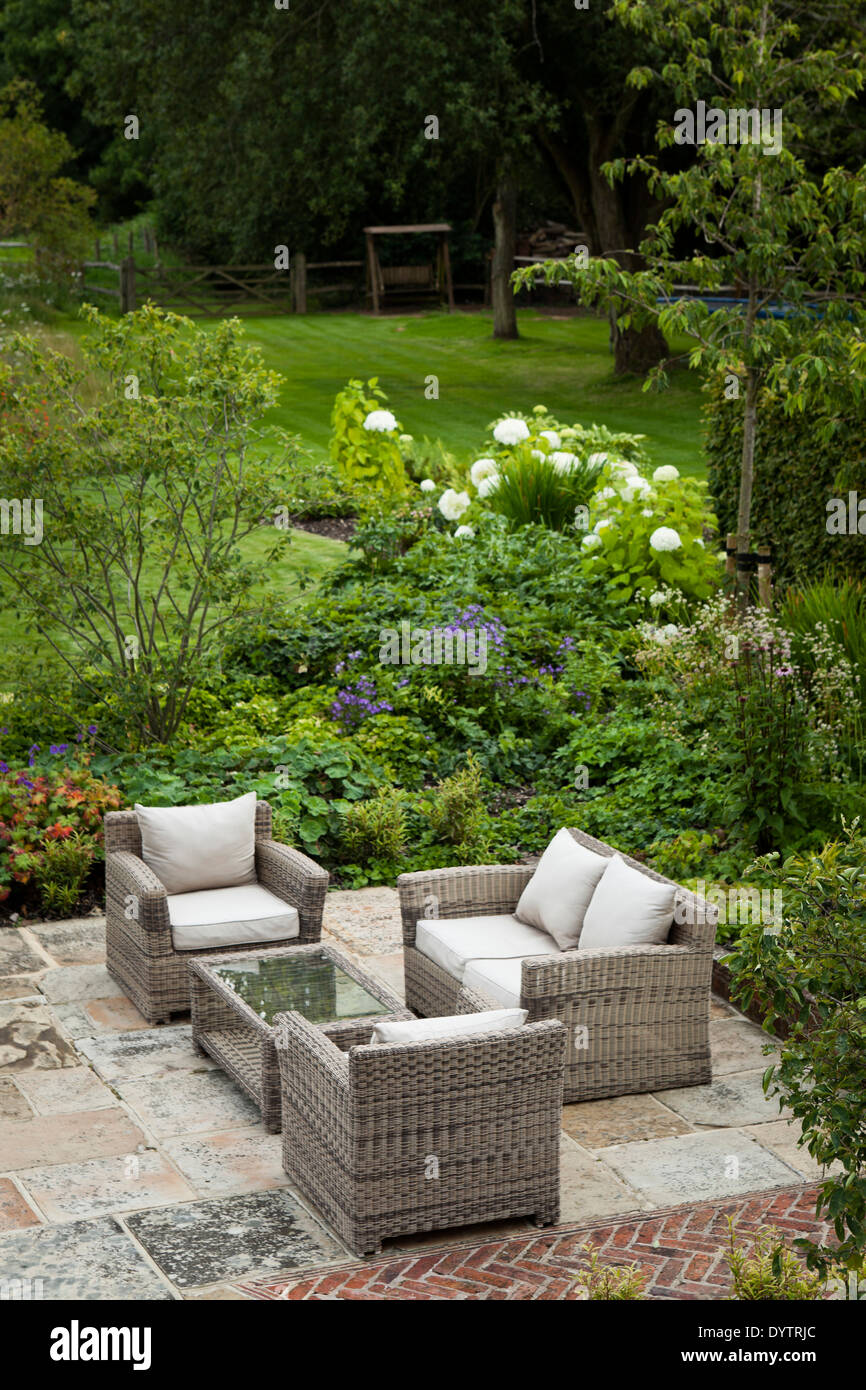York Stone Paved Evening Seating Area And Herring Bone Red Brick Detail  With Cushioned Cane Furniture Adjacent To Bedding And