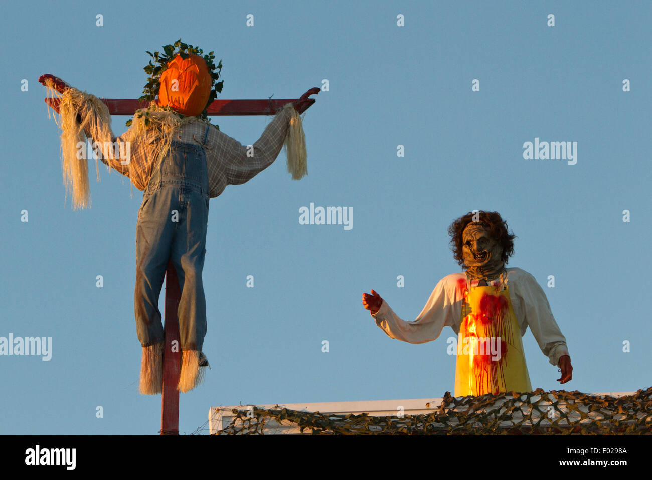 Pumpkin man and zombie woman on rooftop (Halloween decoration ...