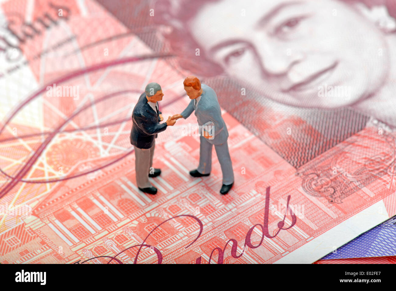 Managers Shaking Hands Miniature Figurines Top British Pound Sterling Banknote