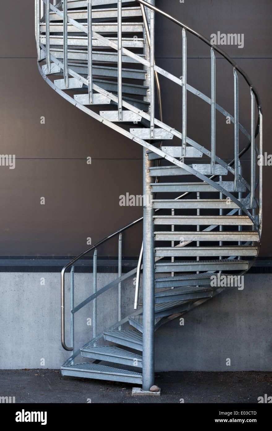 Modern Metal Spiral Staircase Above Dark Gray Wall